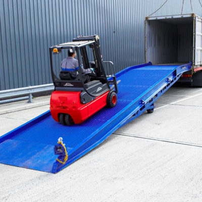 the red forklift driving up on the blue loading ramp into the empty container, easyramps.co.uk - heavy-duty loading ramps uk