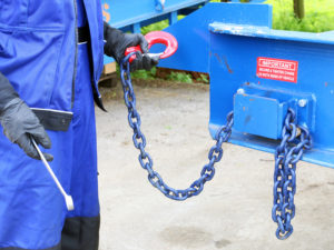 close-up on the man holding chain with red hook and the tool