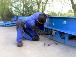 close-up on the man wearing blue work clothes servicing the hydraulic pump of the blue loading ramp