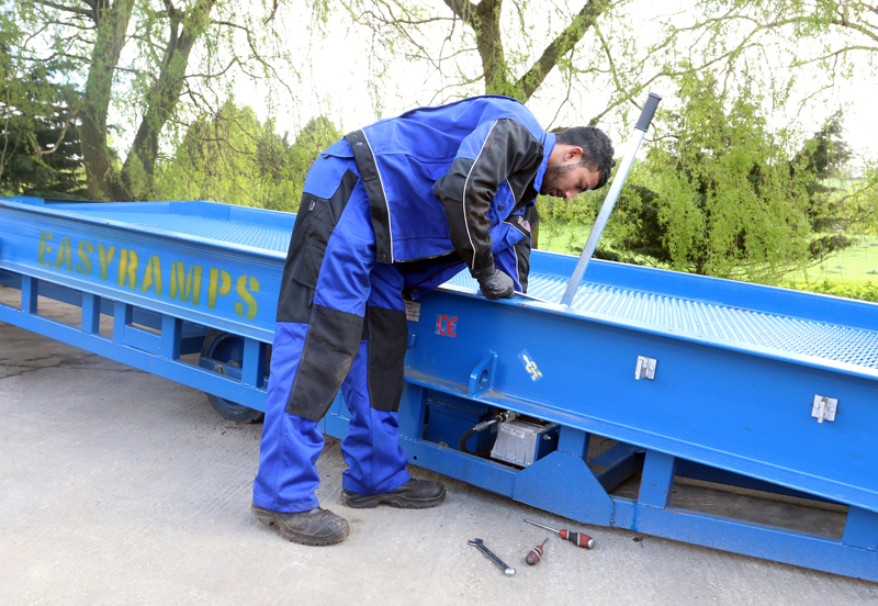 close-up on the man wearing blue work clothes servicing the loading ramp