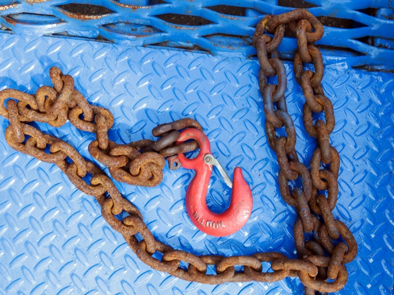 close-up on the blue loading ramps chain with red hook